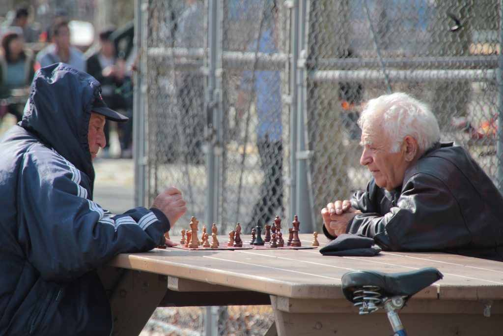 elderly men playing chess on a public table, preparing for their next move