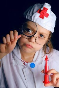 cute child doctor with magnifing glass
